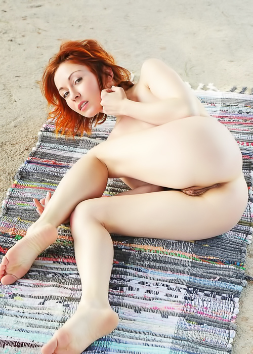 Redhead cutie relaxes naked outdoors