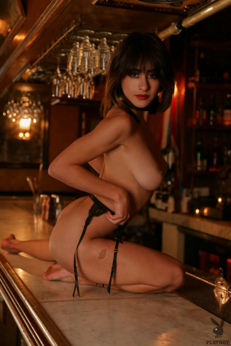 Sexy babe lies down on the bar counter