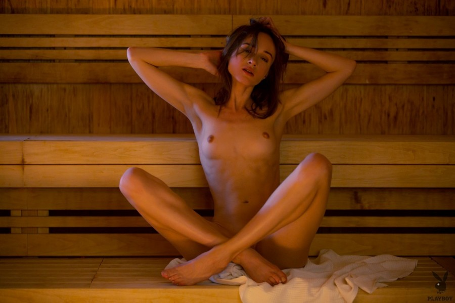 Slim brunette relaxes in hot sauna