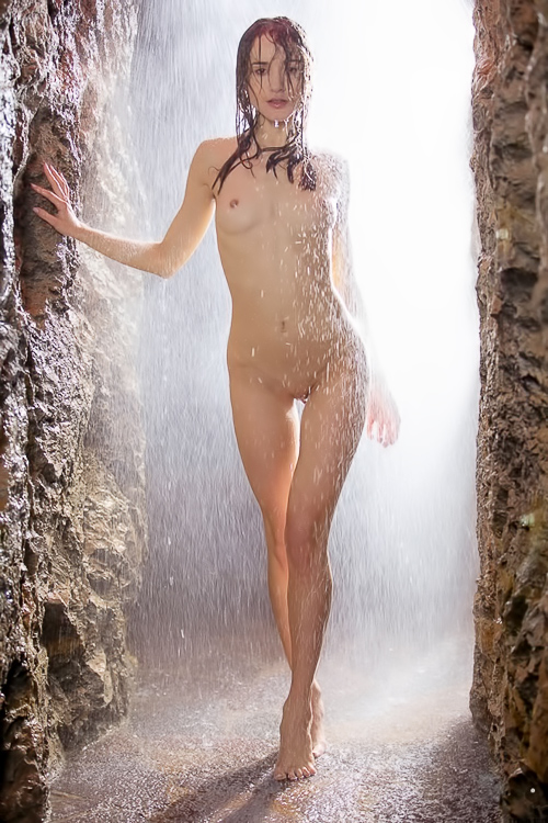 Stunning brunette poses naked in cave