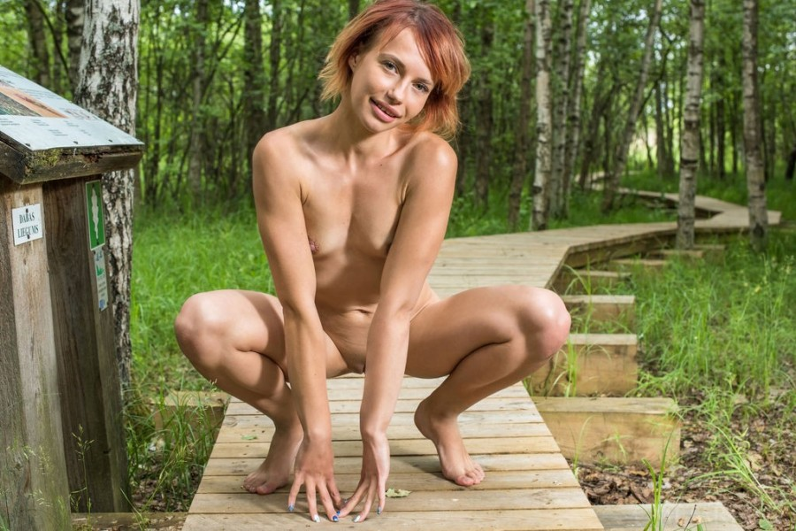 Spreading long legs naked outdoors