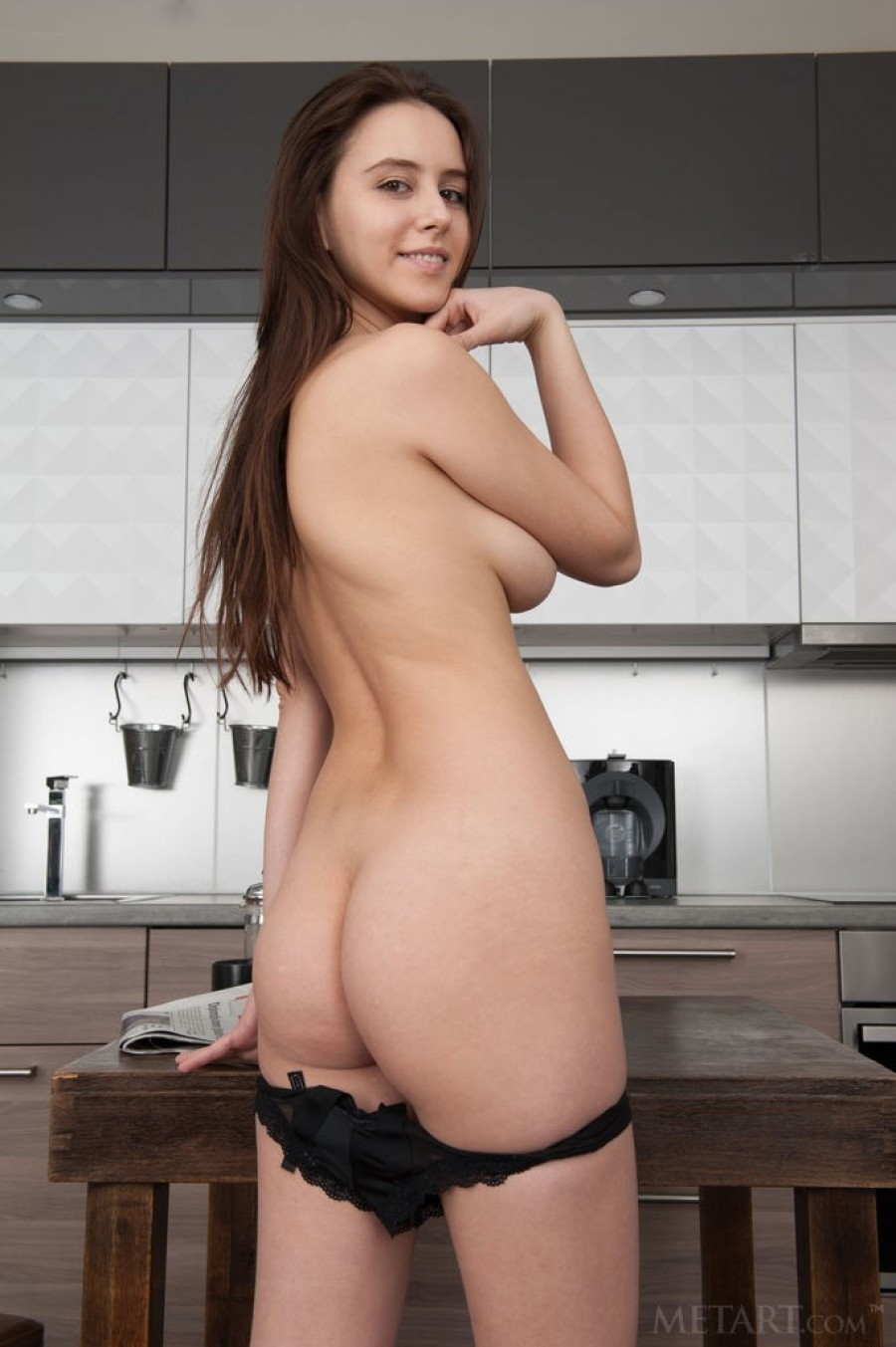 Brunette babe strips in the kitchen