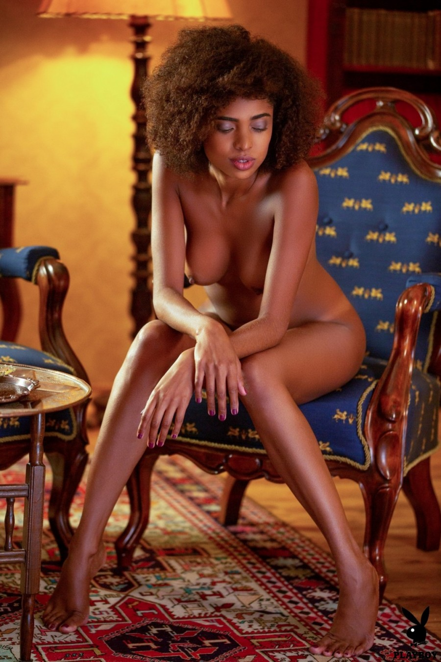 Curly black girl strips and poses