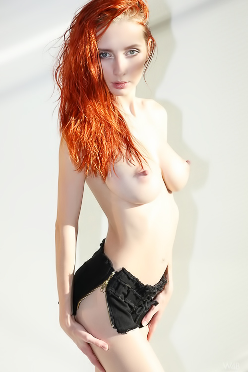 Busty redhead spreading her pussy