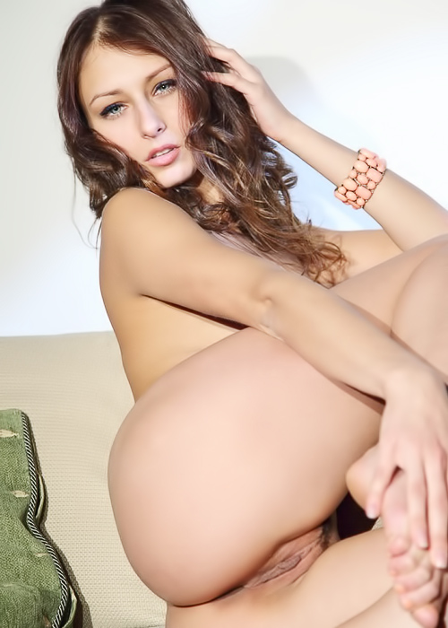 Fantastic brunette poses on the couch