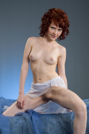 Curly haired redhead naked in bed