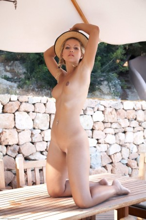 Cutie in hat plays with her round boobs outdoors