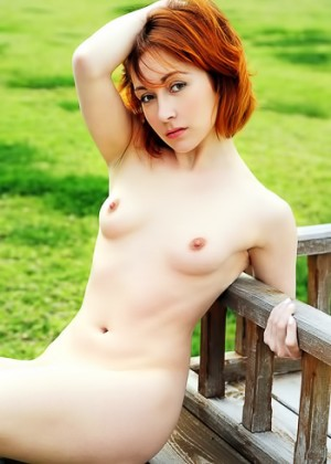 Ginger cutie opens shaved pussy on a bench in the park