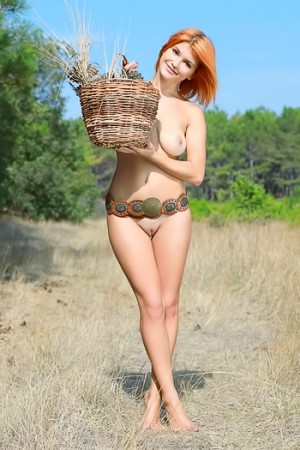 Outdoorsy redhead gathering flowers in the nude
